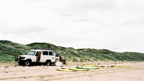 Range rover and surf boards on beach in Sydney
