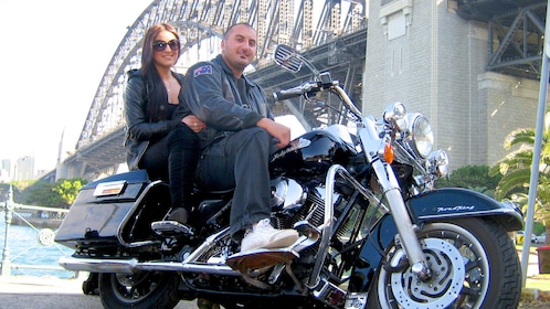 Motorcycle with riders parked in front of Harbour Bridge in Sydney.