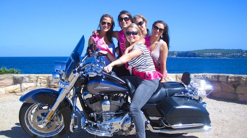 Motorcycle girl group parked on overlook of Sydney Harbour.