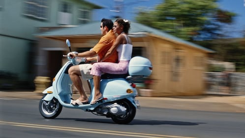 Couple on a scenic ride on a Vespa in Cannes