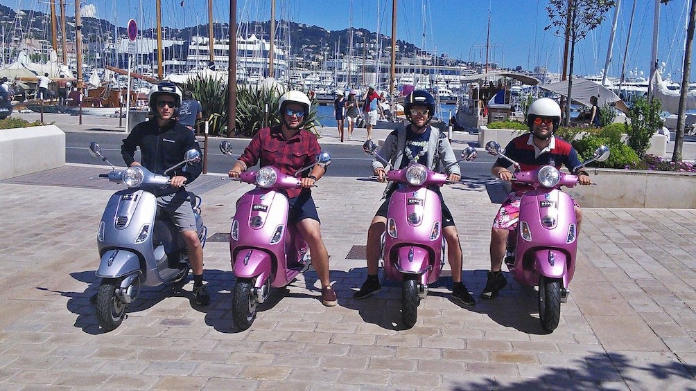 Charger l'élément 3 sur 5. Four tourists riding pink and purple Vespas in Antibes
