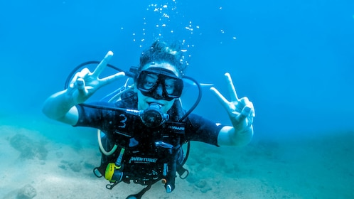 Scuba diving woman flashing peace signs in Puerto Vallarta.
