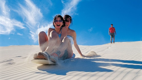 two girls ride a board down sand dune in Perth