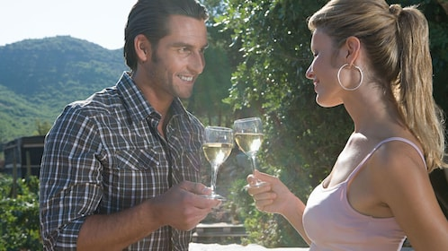 man and woman enjoy glasses of chardonnay at vineyard in Perth