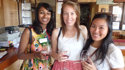 Three girl friends sample wine at winery in Perth