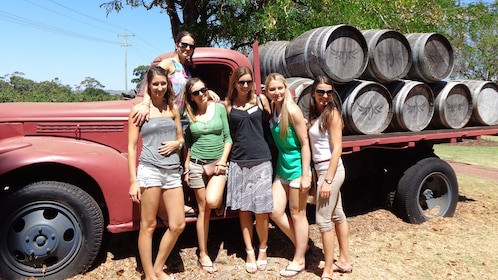 Five friends stand next to truck and wine barrels at winery in Perth