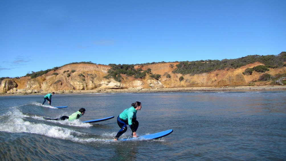 Show item 4 of 5. People surfing on a small wave to the shore of the Great Ocean Road in Australia