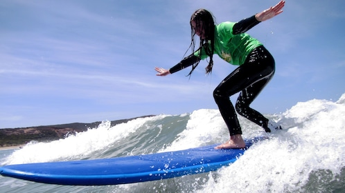 Close up of girl surfer student riding the wave on the Great Ocean Road Surf Lesson in Australia