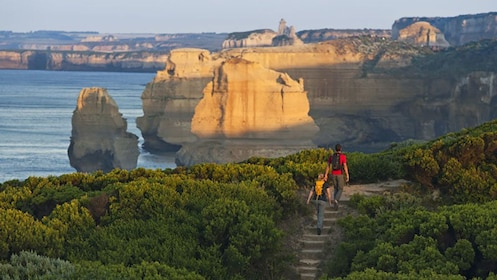 hikers look out beyond cliffs at the ocean in Great Ocean Road