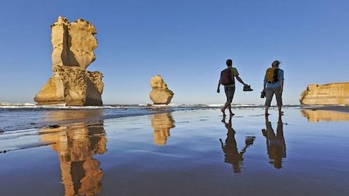 couple walk on beach near sea stacks in Great Ocean Road