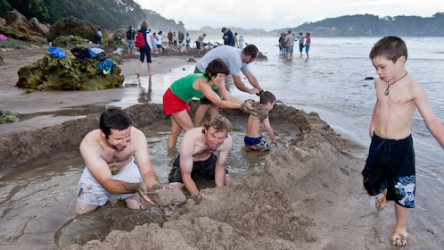Tour group building in sand on Coromandel Peninsula in New Zealand.