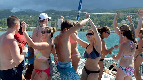 Group of people dancing on a sailboat off the coast of Nevis