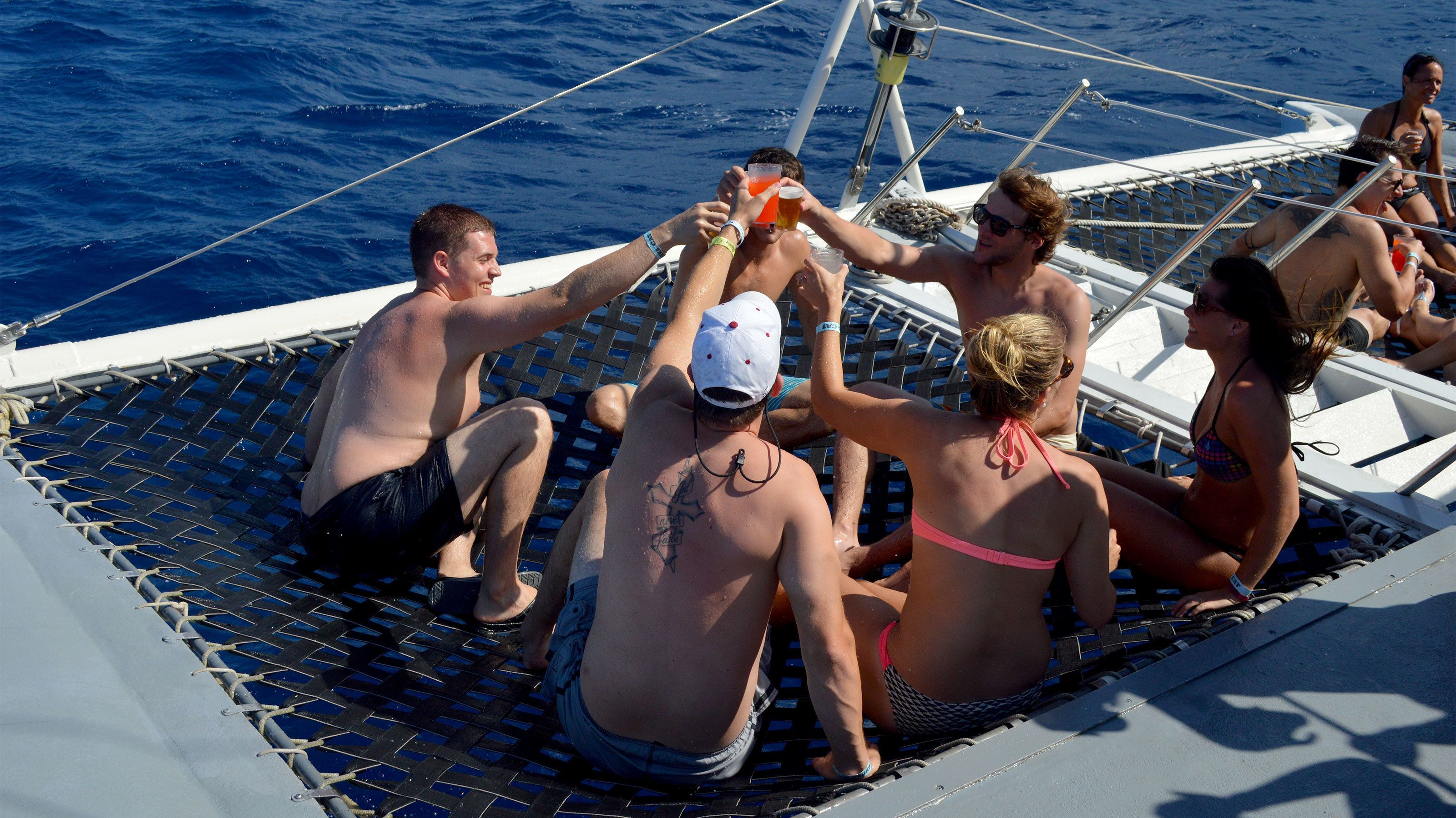 Group of people enjoy drinks and the sun on a sail boat near Nevis