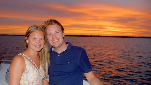 young couple enjoy ride on boat at sunset in Fraser Coast