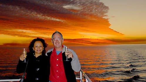 mature couple enjoy ride on boat at sunset in Fraser Coast