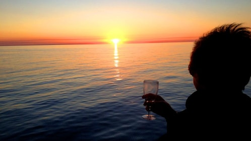 woman with glass of wine looking at sunset over ocean in Fraser Coast