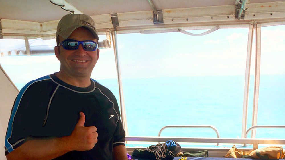 man gives thumbs up on fishing boat in Coral Coast
