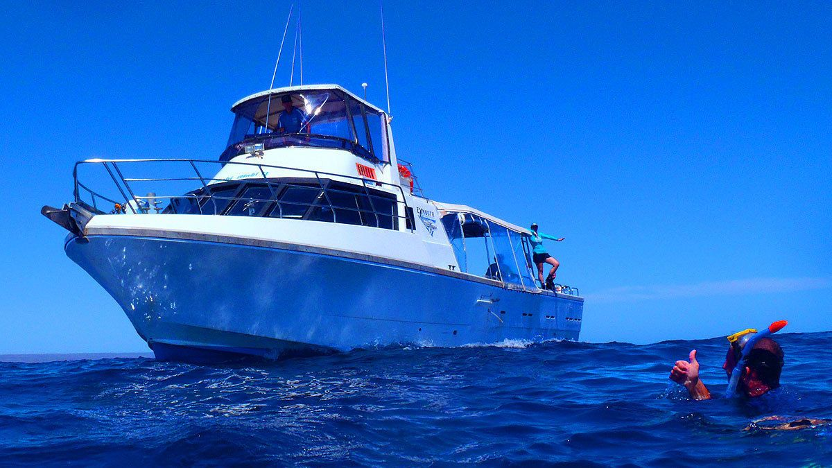 man with snorkeling mask swims next to boat in Coral Coast