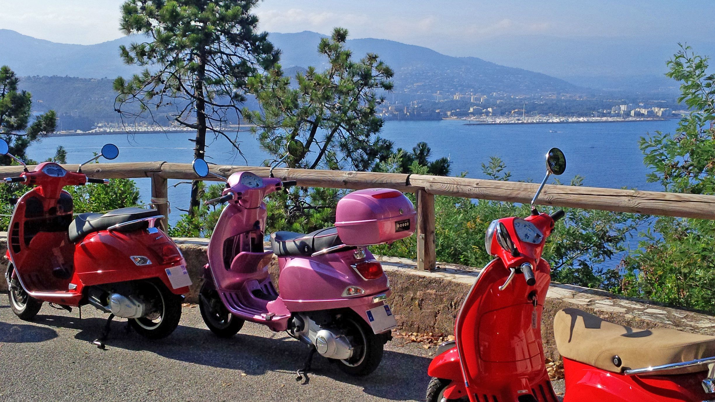 Two red and one pink Vespa parked at a viewpoint in Cannes