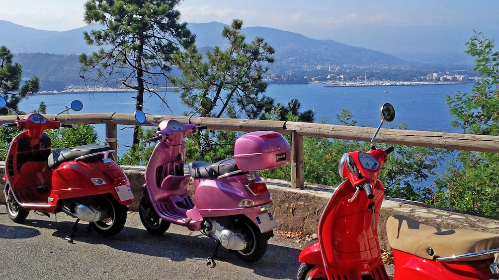 Charger l'élément 2 sur 2. Two red and one pink Vespa parked at a viewpoint in Cannes