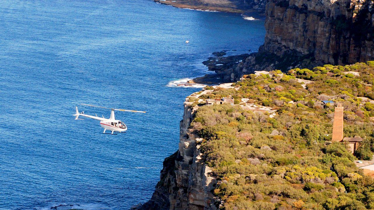 Aerial of helicopter flying over cliffs in Sydney Harbour tour.