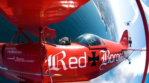 red bi-plane being chased by another bi-plane in Sydney