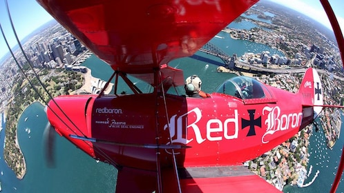red bi-plane flying upside down in Sydney