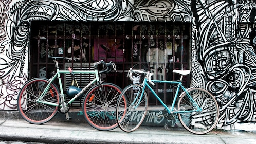 two bicycles parked against colorfully painting building in Melbourne