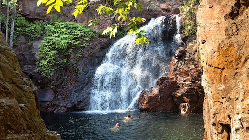 people swimming at the base of a waterfall in Darwin