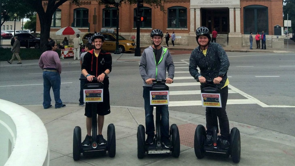 Show item 2 of 5. Three people on segways by a fountain in Dallas