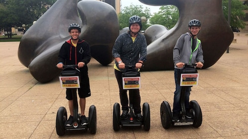 People on segways in front of a sculpture in Dallas