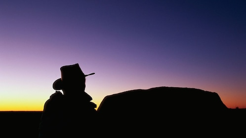 Sunset with girl in hat at Ayers Rock in the Outback of Australia.