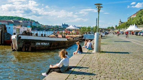 People lounging along the Vltava River in Prague