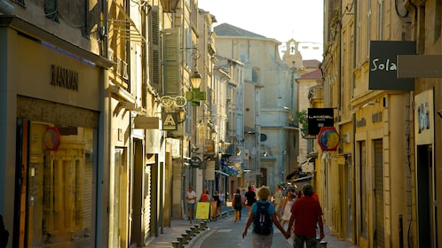 People walking through a narrow street with shops on either side in the town of Avignon