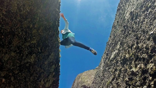 Woman leaping over narrow ravine in Gerêz National Park