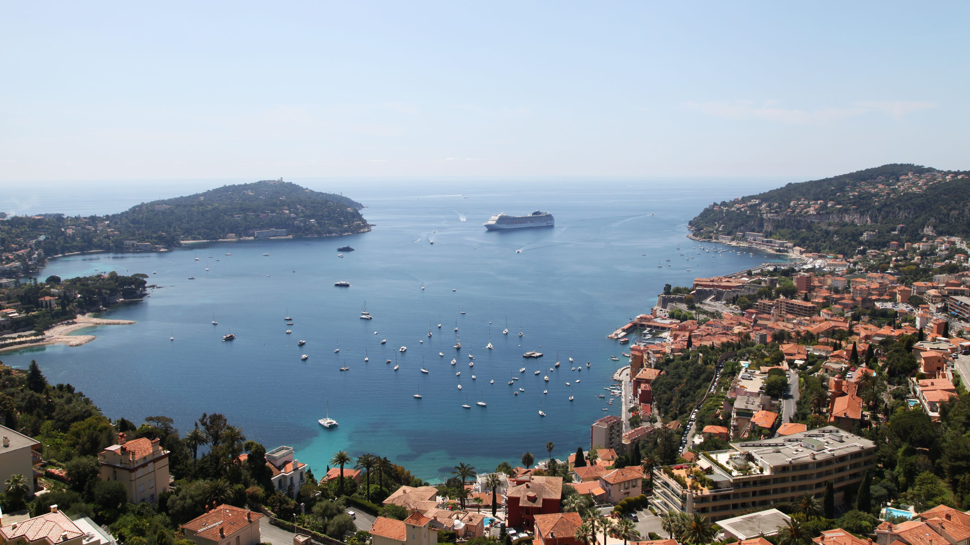 Scattered boats and cruise ship in the clear waters of France
