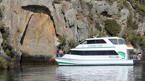 Cruise members on Lake Taupo Scenic Cruise looking at Maori Rock Carvings in New Zealand.