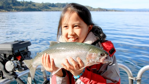 Young girl holding fish on Lake Taupo Scenic Cruise in New Zealand.