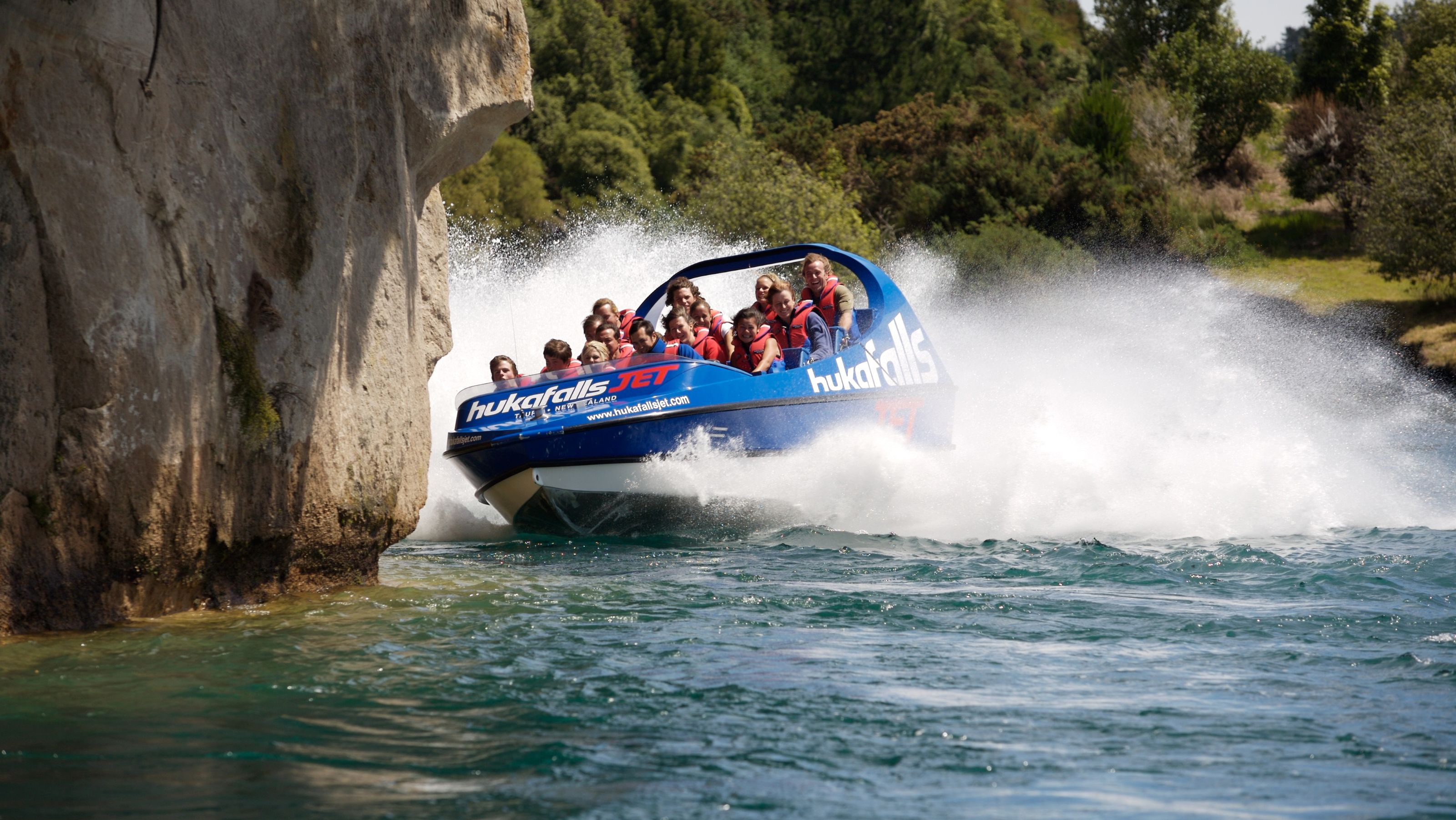 passengers riding in a jet boat near rock wall in Taupo
