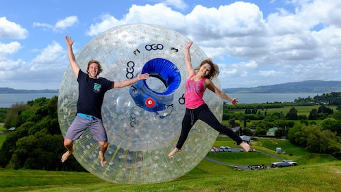 Zorbing orb with couple jumping on grass, Rotorua New Zealand