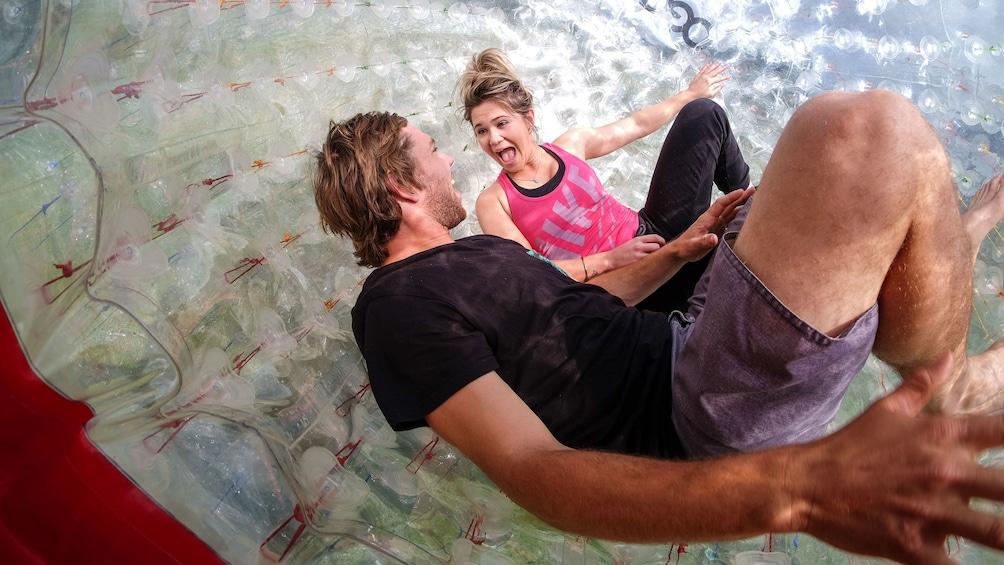 Show item 3 of 4. Rotorua zorbing couple in side plastic orb in New Zealand
