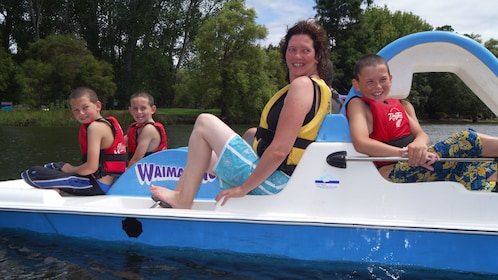 woman with three young boys in paddle boat on lake in Whakatane