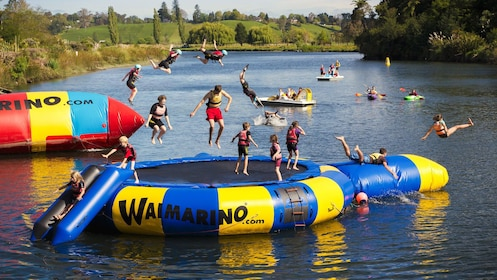 many children enjoy floating trampoline on lake of Whakatane