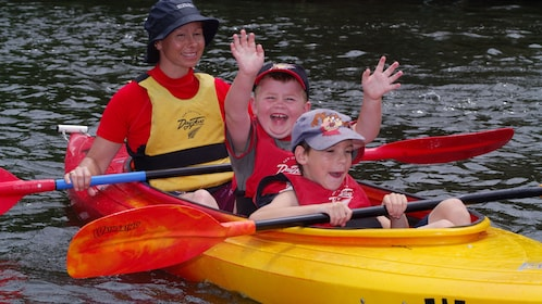 woman and two young boys in kayak on lake in Whakatane