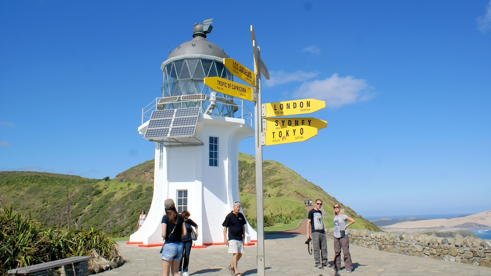 Show item 1 of 8. Direction tower with tourist in Paihia, New Zealand.