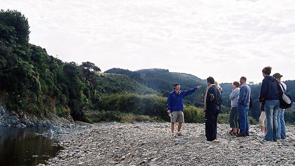 group of people take a walk along rocky beach of Wellington