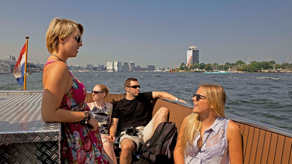 Show item 3 of 8. Cruise guests on deck of boat enjoying sun in Amsterdam