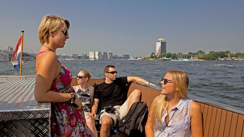 Cruise guests on deck of boat enjoying sun in Amsterdam