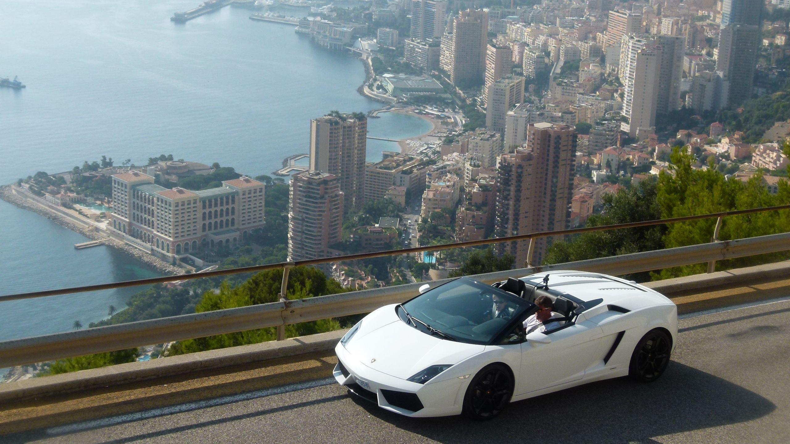 White Lamborghini driving over a bridge in Monaco