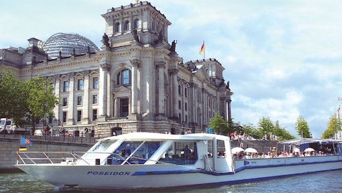 Boat sailing past a historical building on the banks of Spree river in Berlin
